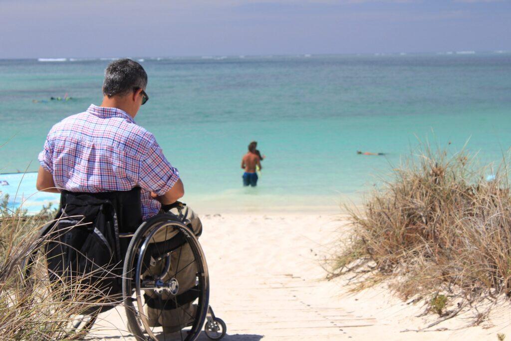Man som sitter i rullstol i stranden
